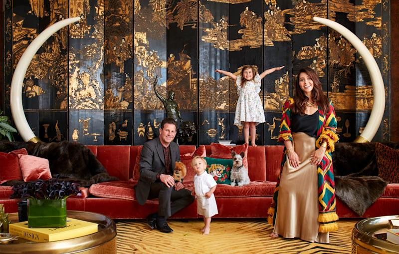 Branden and Rayni Williams, of the Williams & Williams Estates Group in Beverly Hills, relax with their children and dog in their living room, which features a 1920s chinoiserie screen, custom artificial/resin tusks, and a Tai Ping rug. The custom silk sofa is adorned with mink throws and pillows.