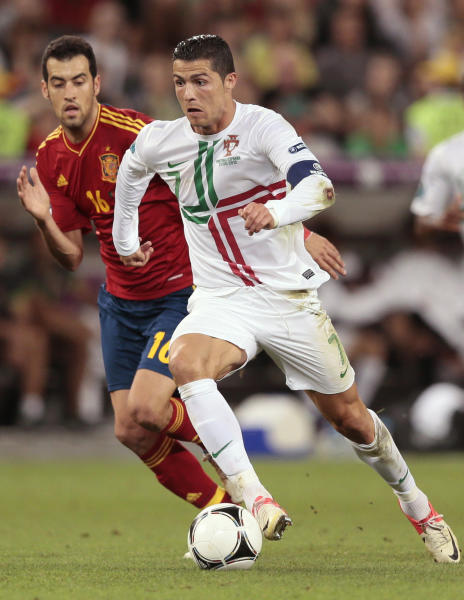 Portugal's Cristiano Ronaldo, right, and Spain's Sergio Busquets vie for the ball during the Euro 2012 soccer championship semifinal match between Spain and Portugal in Donetsk, Ukraine, Wednesday, June 27, 2012. (AP Photo/Ivan Sekretarev)