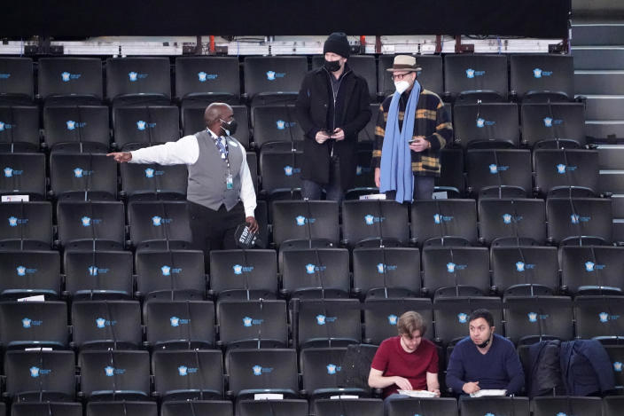 An usher talks to fans before an NBA basketball game between the Brooklyn Nets and the Orlando Magic, Thursday, Feb. 25, 2021, in New York. (AP Photo/Kathy Willens)