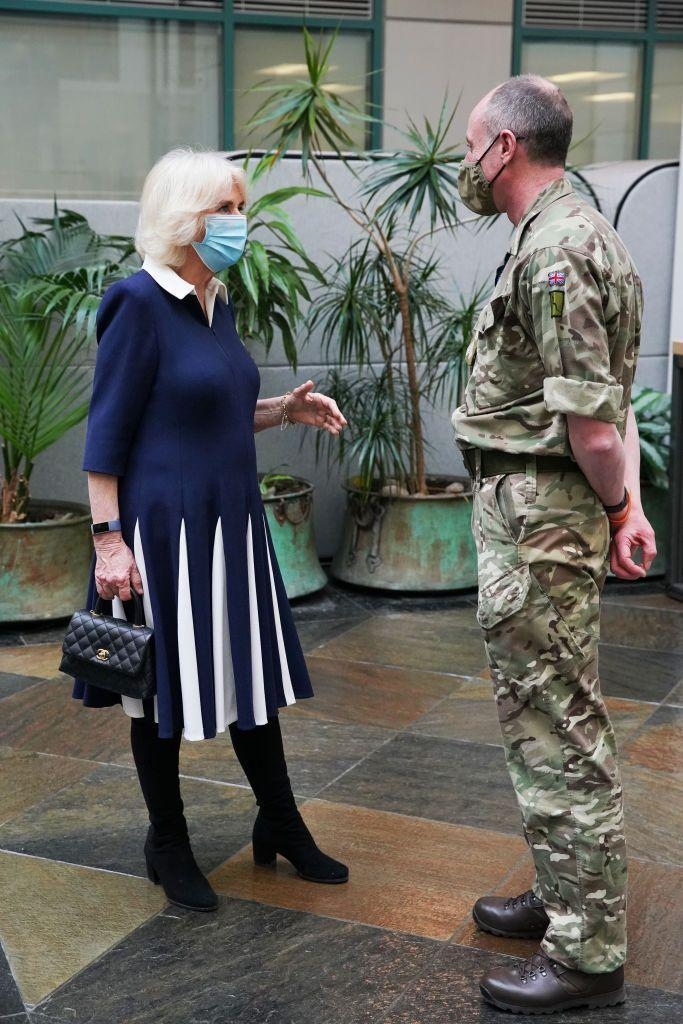 <p>Camilla looked stylish in a navy and white collared dress and black boots during an outing to meet with officials involved in England's vaccine rollout. She paired the look with a black quilted leather Chanel handbag, one of her frequently featured accessories.</p>