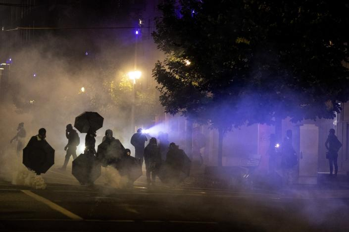 Tear gas fills the air during protests in Portland, Ore., on Friday. (Paula Bronstein/AP)