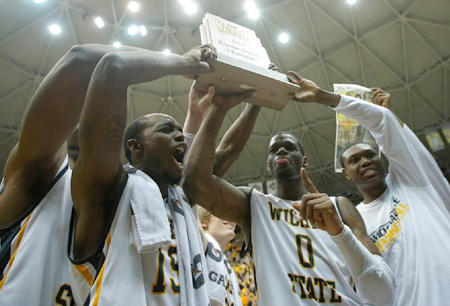 Wichita State players, from left: Nick Wiggins (15), Chadrack Lufile (0) and Cleanthony Early, right, hold up the Missouri Valley Conference regular season trophy after beating Missouri State 68-45 in an NCAA college basketball game in Wichita, Kan., Saturday, March 1, 2014. (AP Photo/The Wichita Eagle, Travis Heying)