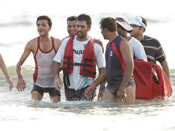 India's captain Mahendra Singh Dhoni is surrounded by his fans after he spent time in the Arabian sea after India won the One-Day International match series against Australia by 1-0. (AP Photo)