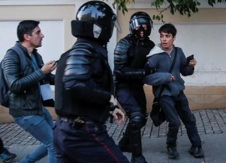Law enforcement officers detain a man after a rally to demand authorities allow opposition candidates to run in the upcoming local election in Moscow