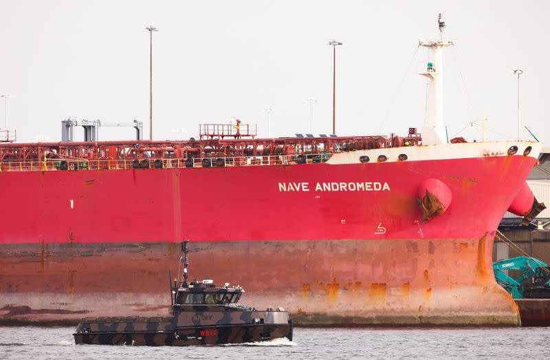 A military boat passes in front of the Liberia-flagged oil tanker Nave Andromeda at Southampton Docks, following a security incident aboard the ship the night before off the coast of Isle of Wight, in Southampton