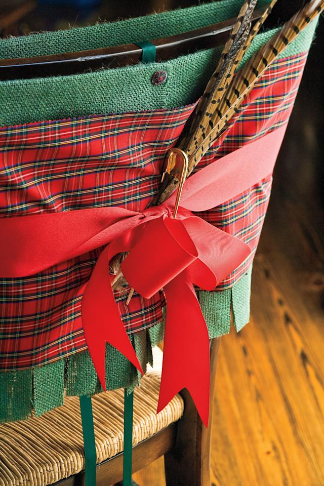 <p>Outfit your everyday dining room chairs in their Christmas best. Wrap your chairs in a merry cummerbund fashion, using a band of burlap as the base, and tartan on top. Tie with wide red grosgrain ribbon, and secure all cloth with an oversize laundry pin. Add a few jaunty pheasant feathers, and use scissors to make inch-wide cuts along the bottom of the burlap for a frilled, fringe look. Customize the fabric choices and color schemes to fit your own home's holiday décor. We suggest staying away from fabric with glitter – when guests lean back on their chairs, the glitter tends to rub off.</p>