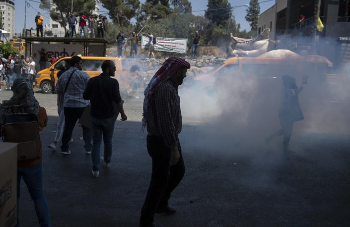 Riot police use teargas to disperse angry demonstrators before dispersing them during a rally protesting the death of Nizar Banat, an outspoken critic of the Palestinian Authority, in the West Bank city of Ramallah, Thursday June 24, 2021. Banat who was a candidate in parliamentary elections called off earlier this year died after Palestinian security forces arrested him and beat him with batons on Thursday, his family said. (AP Photo/Nasser Nasser)