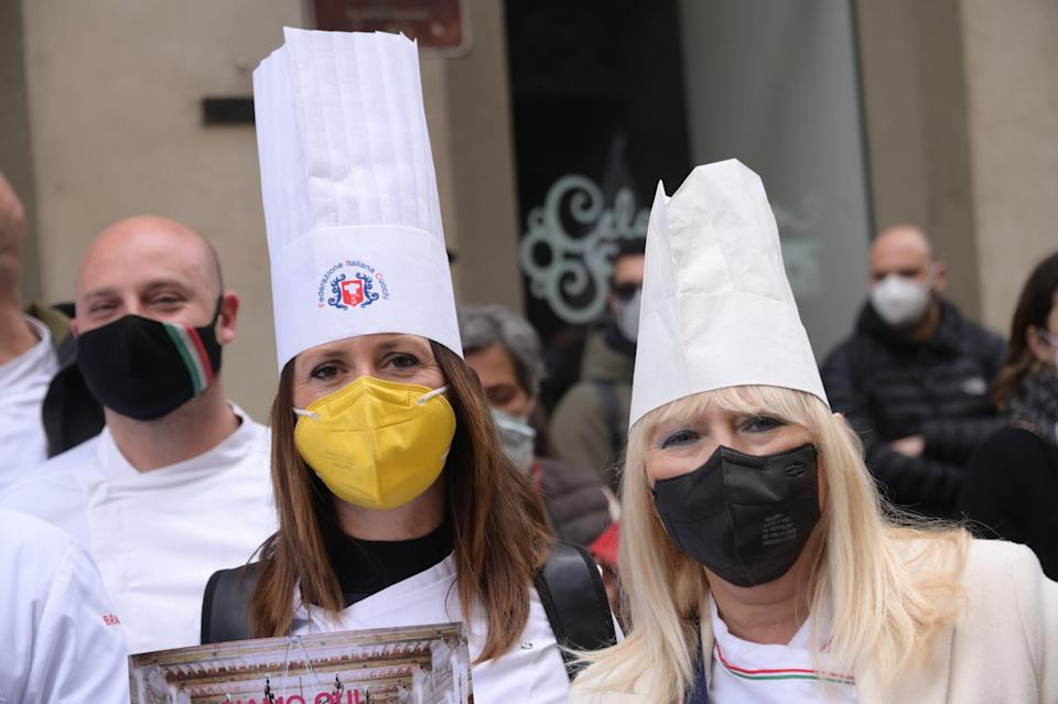 FLORENCE, ITALY - APRIL 13: women wearing face masks and chef's hats protest against the closure of restaurants on April 13, 2021 in Florence, Italy. Italian small business owners, restaurants and non-primary activities are protesting as their businesses are shut for weeks and 250k jobs have been lost due to COVID-19 lockdown. (Photo by Paolo Lo Debole/Getty Images) (Photo: Paolo Lo Debole via Getty Images)