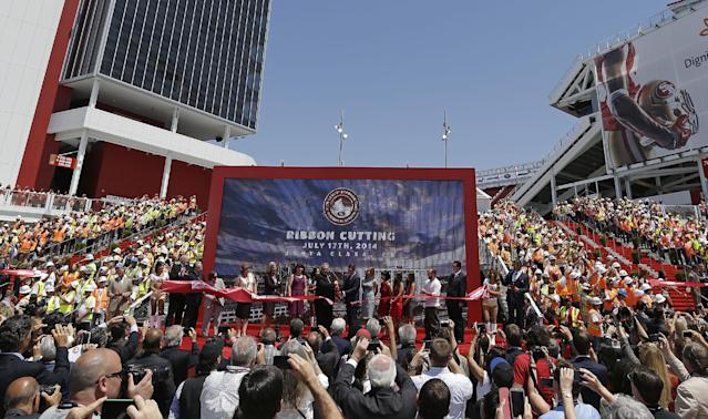 Construction workers stand on each side of the stage and watch the ribbon-cutting and opening of Levi's Stadium Thursday, July 17, 2014, in Santa Clara, Calif. The San Francisco 49ers held a ribbon-cutting ceremony to officially open their new home. The $1.2 billion Levi's Stadium, which took only about 27 months to build, also will host the NFL Super Bowl in 2016 and other major events. (AP Photo/Eric Risberg)