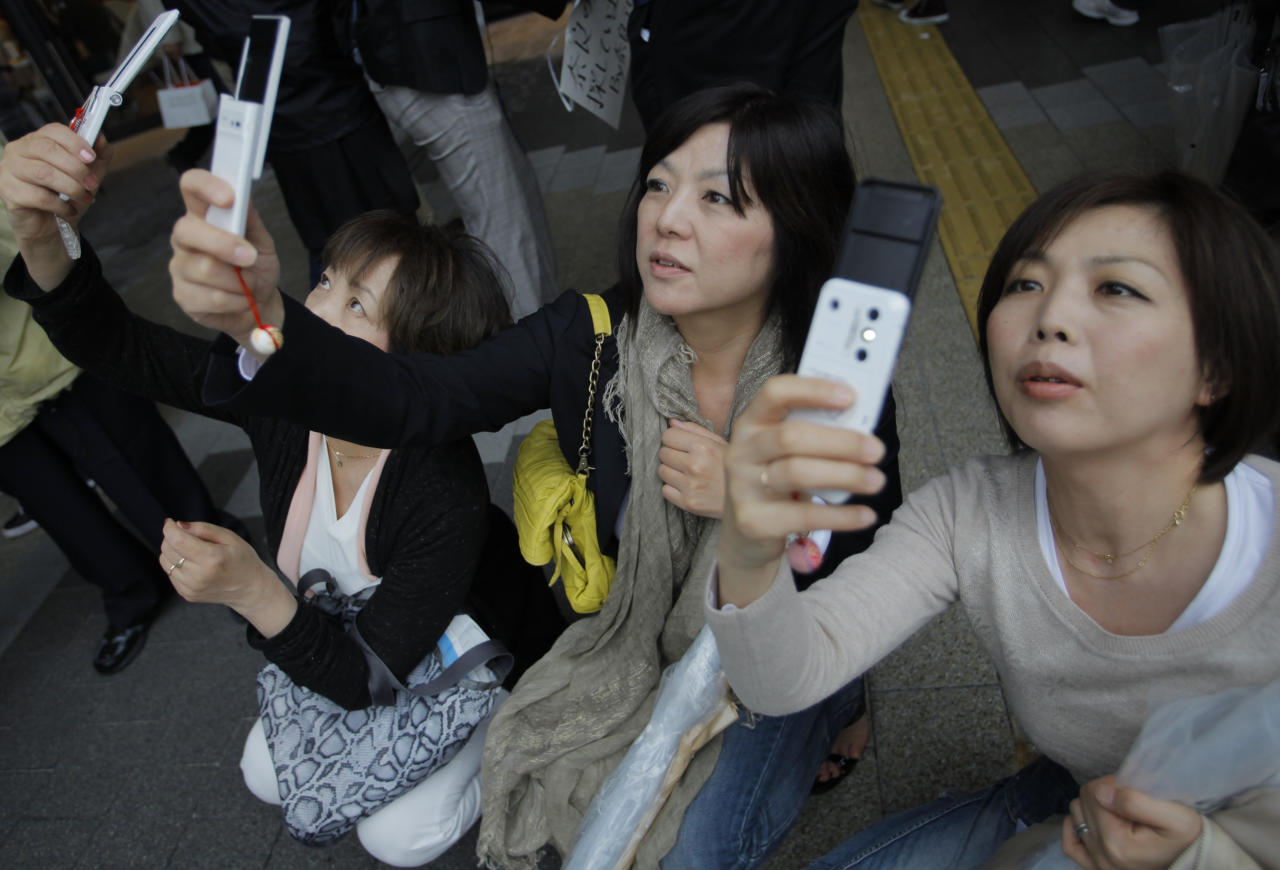 Visitors take photos of the Tokyo Skytree at its grand opening in Tokyo, Tuesday, May 22, 2012. The world's tallest tower and Japan's biggest new landmark opened to the public on Tuesday. (AP Photo/Itsuo Inouye)