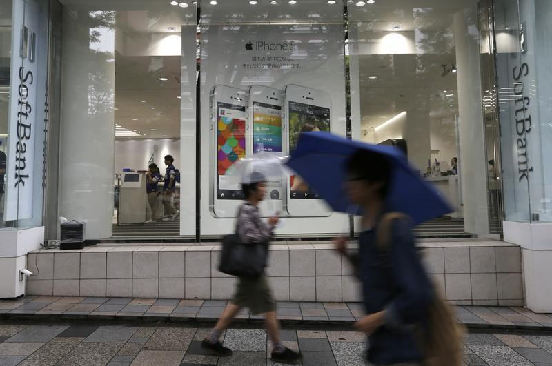 Passersby walk in front of a SoftBank Corp branch in Tokyo