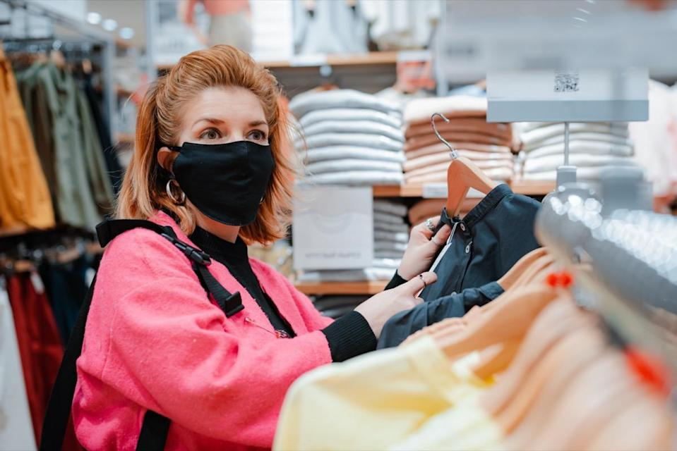 woman with phone bright pink shopping Mall coat with black protective mask on her face from virus infected air. concept of virus protection in the fashion, beauty, and shopping industries