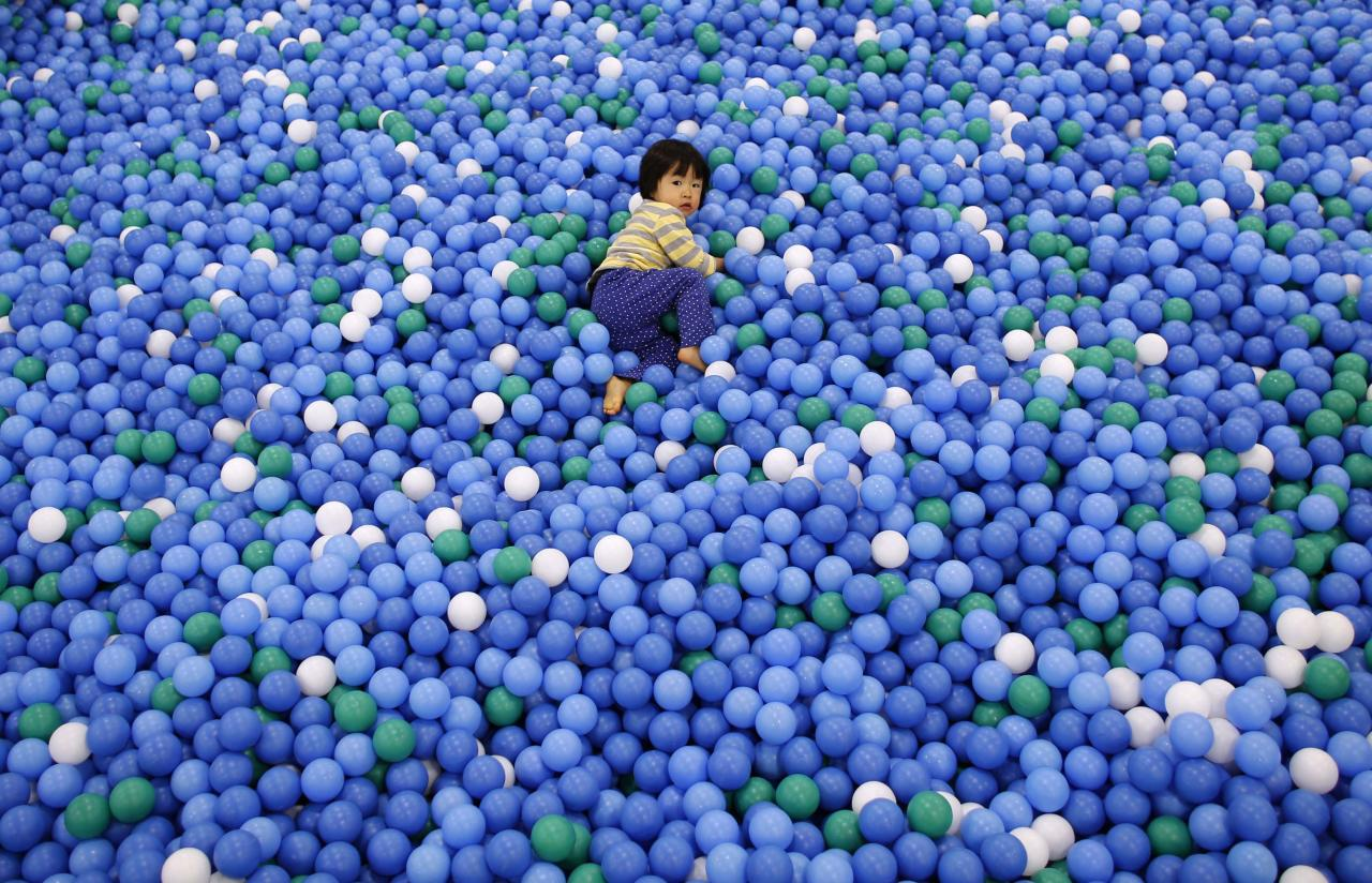 Two-year-old Nao Watanabe plays in a ball pit at an indoor playground which was built for children and parents who refrain from playing outside because of concerns about nuclear radiation in Koriyama, west of the tsunami-crippled Fukushima Daiichi nuclear power plant, Fukushima prefecture February 27, 2014. March 11 marks the third anniversary of the earthquake and tsunami that devastated Japan�s Fukushima Daiichi nuclear power plant. In Koriyama, a short drive from the crippled Fukushima nuclear plant, the city recommended shortly after the disaster that children up to two years old not spend more than 15 minutes outside each day. Those aged 3 to 5 should limit their outdoor time to 30 minutes or less. The limits were lifted last year, but many kindergartens and nursery schools continue to obey them even now in line with the wishes of worried parents. An annual survey by the Fukushima prefecture Board of Education found that children in Fukushima weighed more than the national average in virtually every age group. The cause seems to be a lack of exercise and outdoor activity. Picture taken February 27, 2014. REUTERS/Toru Hanai (JAPAN - Tags: DISASTER EDUCATION ENVIRONMENT HEALTH TPX IMAGES OF THE DAY)