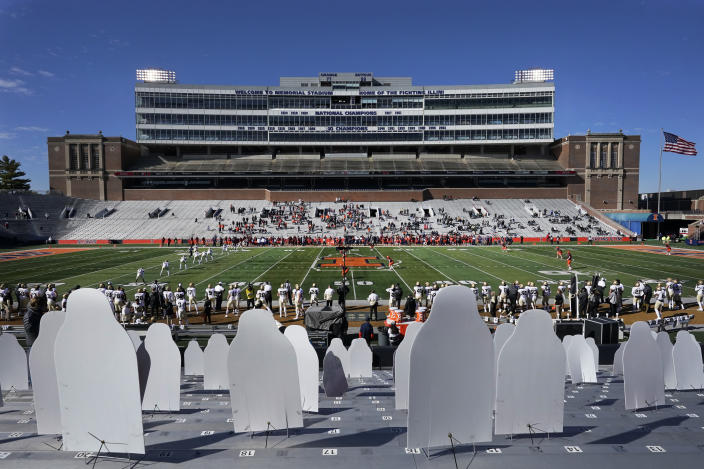Cardboard cutouts of Illinois football fans are erected in the east seats of Memorial Stadium as family members of both Illinois and Purdue players occupy the west seats during the first half of an NCAA college football game Saturday, Oct. 31, 2020, in Champaign, Ill. (AP Photo/Charles Rex Arbogast)