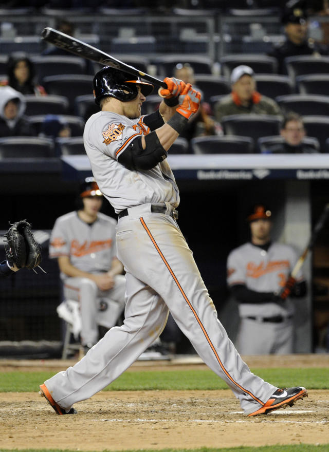 Baltimore Orioles' Chris Davis hits a sacrifice fly to score Jonathan Schoop during the ninth inning of a baseball game against the New York Yankees on Wednesday, April 9, 2014, at Yankee Stadium in New York. The Orioles won 5-4. (AP Photo/Bill Kostroun)