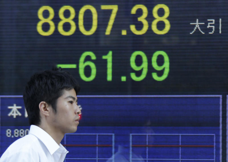 A man walks by an electronic stock board of a securities firm showing Japan's Nikkei 225 index that dropped 61.99 points to close at 8,807.38 for the day in Tokyo Tuesday, Sept. 11, 2012. Asian stock markets retreated Tuesday as investors sought safety ahead of critical events this week that will test Europe's willingness to unite in order to deal with a major debt crisis. (AP Photo/Koji Sasahara)