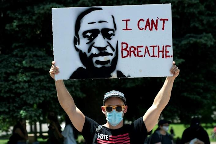 A demonstrator holds up a poster with a rendition of George Floyd on May 30 in Denver (AFP Photo/Jason Connolly)
