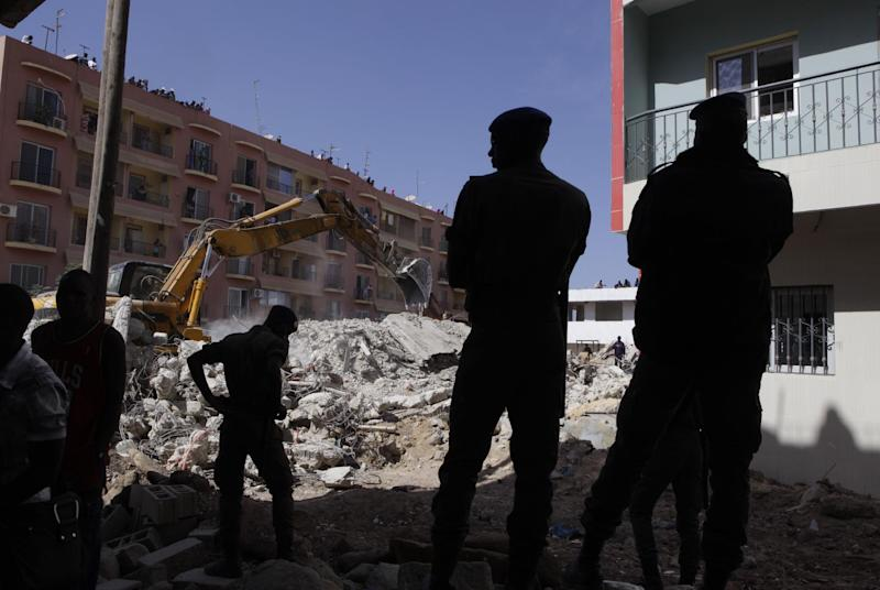 Police secure the area as workers clear rubble from the site of a four-storey building that collapsed during construction, in a neighborhood full of buildings under construction, in Dakar, Senegal, Friday, March 8, 2013.  Omar Samb Gueye, the local chief of the Ouakam area where the building was being constructed, said two people were killed and two injured when the building folded in on itself and collapsed in Senegal's capital, Dakar.  He said the building was being constructed twice as tall as the two-storey height for which it had been authorized. (AP Photo/Rebecca Blackwell)