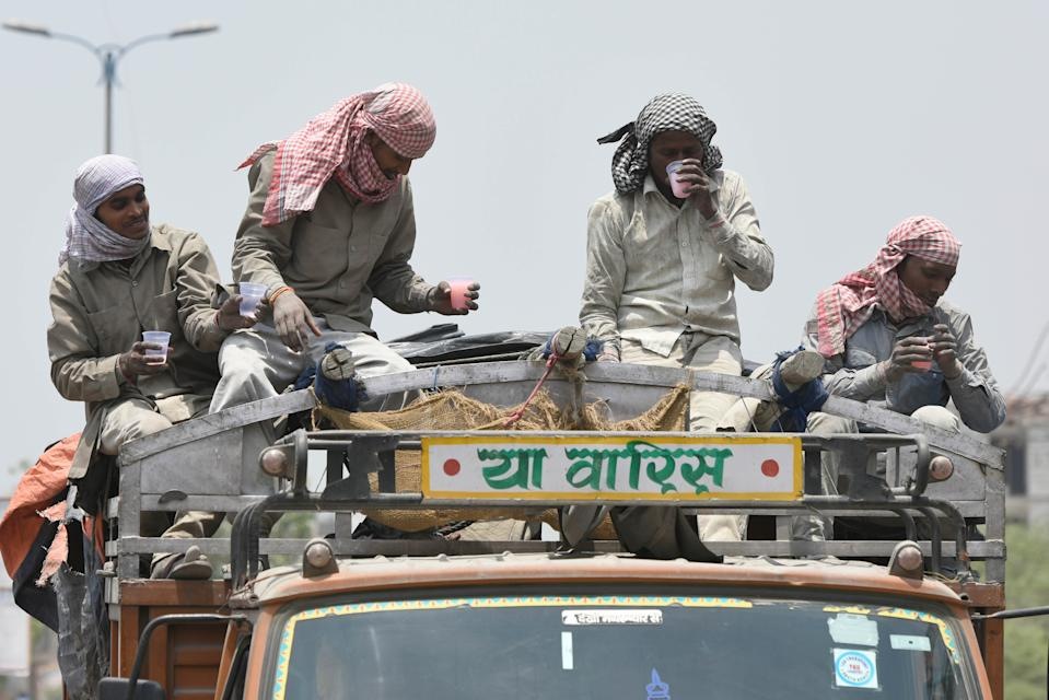 NEW DELHI, INDIA - JUNE 9: A group of labourers sitting atop a truck drink flavoured water, distributed by local residents as a goodwill gesture on a summer day, at Chattarpur, on June 9, 2019 in New Delhi, India. The national capital reeled under scorching heat Saturday, with high humidity adding to the discomfort of the residents. Delhi is expected to record a high of 44 and a low of 29 degrees Celsius, a MeT official said. (Photo by Burhaan Kinu/Hindustan Times via Getty Images)