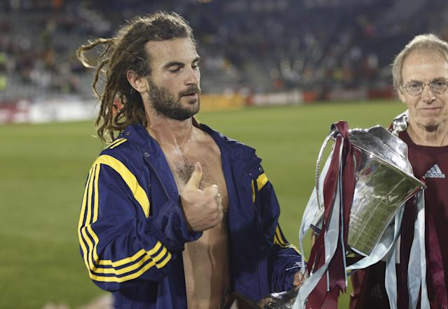 Real Salt Lake midfielder Kyle Beckerman gestures as he claims the Rocky Mountain Cup after the team's 1-0 victory over the Colorado Rapids in a soccer game in Commerce City, Colo., on Saturday, Aug. 2, 2014. With the win, Real Salt Lake claimed the Rocky Mountain Cup, which is awarded to the winner of the teams' regular-season schedule. (AP Photo/David Zalubowski)