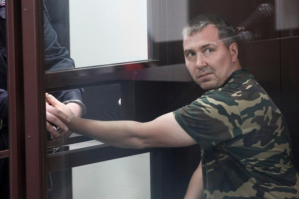 Alexander Popov, a man who was arrested on suspicion of murder sits behind the glass in a courtroom in the city of Gorodets, 60 km. (36 miles) north-west of Nizhny Novgorod, Russia, Sunday, June 20, 2021. (AP)