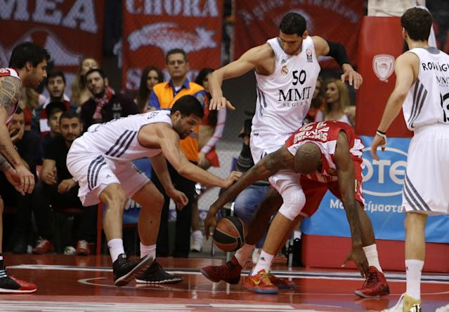 Olympiakos' Cedric Collins, right, fights for the ball with Real Madrid's Felipe Reyes, left, and Salah Mejri during a Euroleague playoff game 3 basketball match at the Peace and Friendship Arena in Athens' port of Piraeus on Monday April 21, 2014. (AP Photo/Thanassis Stavrakis)