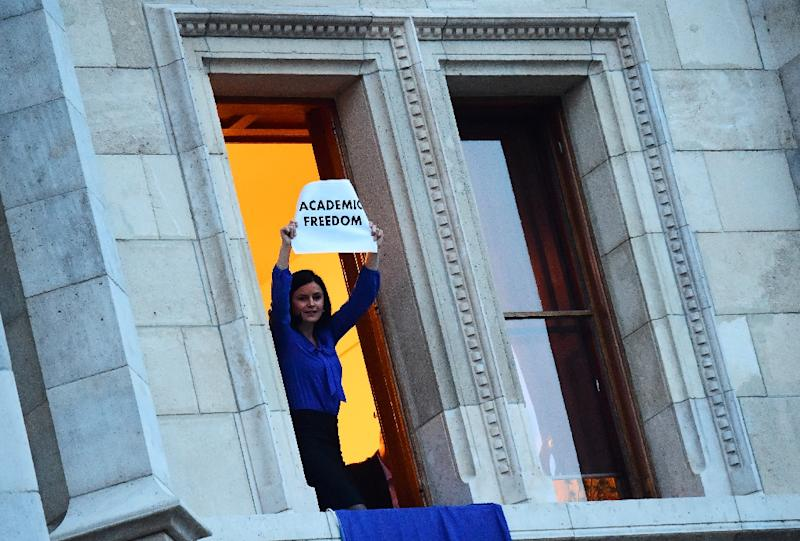 Member of Parliament Agnes Kunhalmi of the Hungarian Socialist Party displays an EU flag at the window of an office room in the parliament building as protesters gather below on April 4, 2017 (AFP Photo/ATTILA KISBENEDEK)