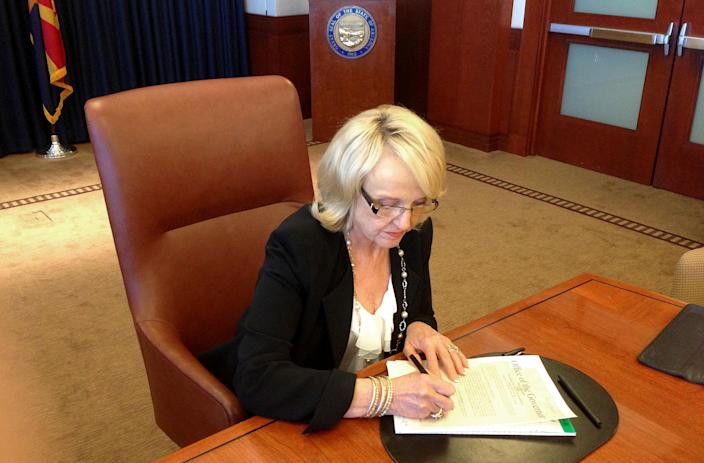 In this photo provided by by Ariz. Rep. Jeff Dial, Gov. Jan Brewer signs a proclamation calling the Legislature into special session, Tuesday, June 11, 2013, in Phoenix. Brewer acted after weeks of House delays in considering the state budget and her Medicaid expansion proposal. (AP Photo/Courtesy of Jeff Dial)