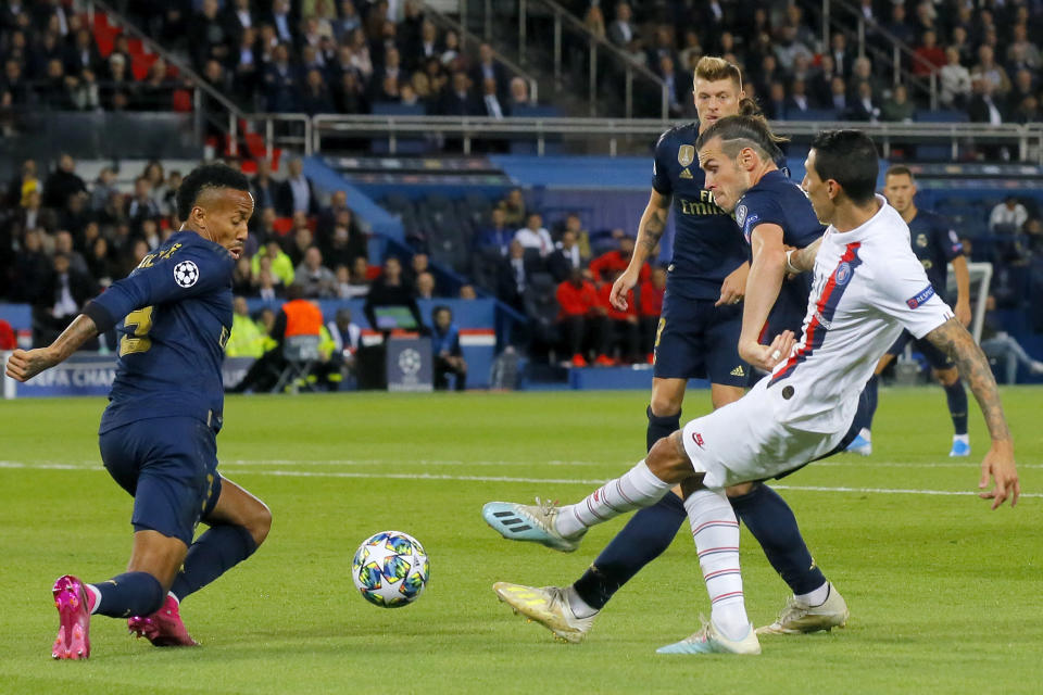 PSG's Angel Di Maria shoots the ball between Real Madrid's Gareth Bale and Eder Militao, left, during the Champions League group A soccer match between PSG and Real Madrid at the Parc des Princes stadium in Paris, Wednesday, Sept. 18, 2019. (AP Photo/Michel Euler)