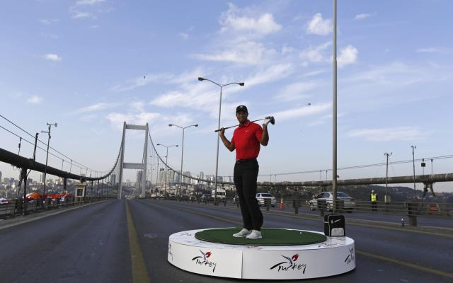 U.S. golfer Tiger Woods poses during an event to promote the upcoming Turkish Airlines Open golf tournament, on the Bosphorus Bridge that links the city's European and Asian sides, in Istanbul November 5, 2013. Woods is in Turkey to attend the tournament, which will take place in Antalya, southern Turkey, between November 7 to 10. REUTERS/Murad Sezer (TURKEY - Tags: SPORT GOLF)
