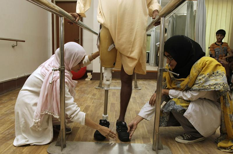 In this picture taken on Saturday, March 30, 2013,  Pakistani female doctors help a disabled child at a rehabilitation center at the Dow Medical Institute for Health in Karachi, Pakistan. In a country better known for honor killings of women and low literacy rates for girls, Pakistan's medical schools are a reflection of how women's roles are evolving. Women now make up the vast majority of students studying medicine, a gradual change that's come about after a quota favoring male admittance into medical school was lifted in 1991. (AP Photo/Fareed Khan)