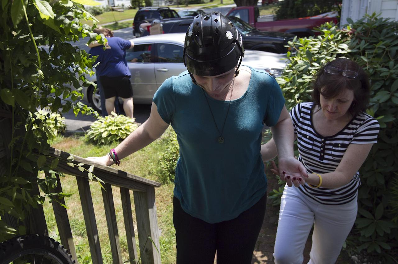 In this Thursday, Aug. 2, 2012 photo, Meg Theriault is assisted by her mother, Deb Theriault, right, as she arrives at their home in Salisbury, Mass., for the first time since she was involved in a multi-fatal minivan crash in New Zealand on May 12, 2012. Meg survived the accident that killed three fellow Boston University students, all of them finishing a semester of study in Australia. But she was far from unscathed. The brain injuries she sustained were serious; it was an open question whether she would ever again be the high-spirited young woman she was before the crash. (AP Photo/Steven Senne)