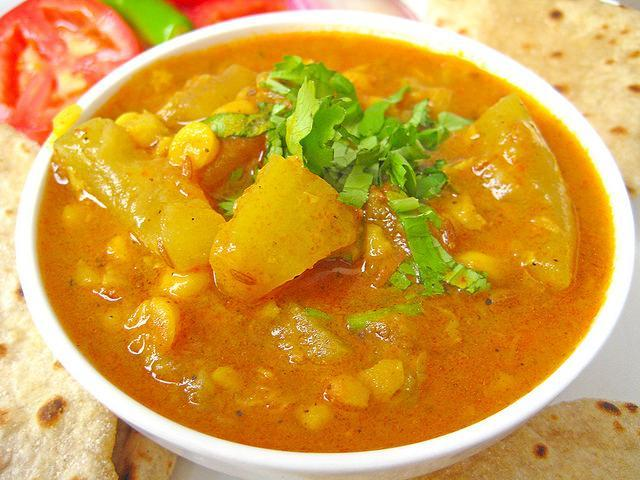 """<p>A healthy dal preperation made with Chana dal (bengal gram) & lauki (bottle gourd). Soak 1/2 cup chana dal for 1-2 hours & rinse. In a pressure cooker, add 1 tsp oil & crackle some cumin. Add hing, one chopped onion, one chopped green chili, some ginger & one chopped tomato. Mix well. Add turmeric powder, shili powder & coriander powder to taste. Add rinsed chana dal & one cup chopped lauki with some salt. Add enough water & pressure cook till done. """"Creative Commons Lauki Chana Dal"""" by Soniya Goyal is licensed under CC BY 2.0 </p>"""