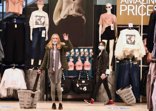 A shopper waves as she enters the Primark store in Oxford Street, London