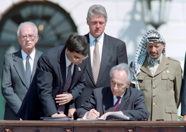 Israeli foreign minister Shimon Peres signs the Oslo Accords on September 13, 1993 in a ceremony at the White House