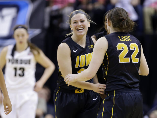 Iowa guards Samantha Logic (22) and Melissa Dixon celebrate late in the second half of an NCAA college basketball game against Purdue in the quarterfinals of the Big Ten women's tournament in Indianapolis, Friday, March 7, 2014. Iowa defeated Purdue 87-80. (AP Photo/Michael Conroy)