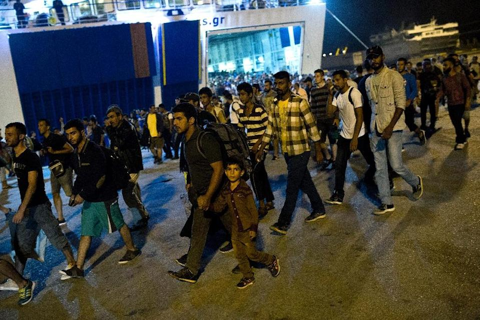 Migrants disembark from a ferry at the port of Piraeus in Athens on September 1, 2015 (AFP Photo/Angelos Tzortzinis)