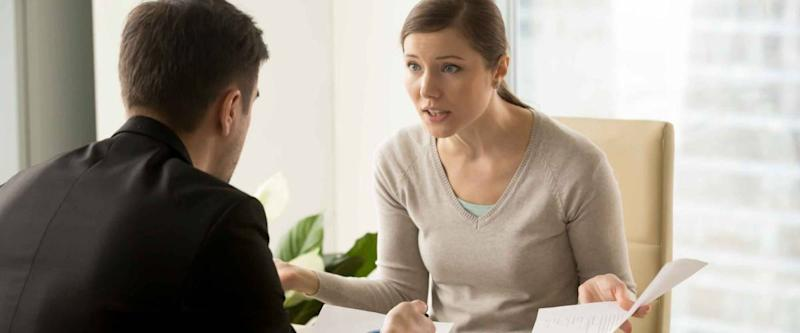 Angry businesswoman arguing with businessman about paperwork