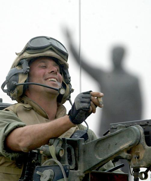 FILE - In this April 9, 2003 file photo, Staff Sgt. Nick Popaditch of the 3rd Battalion, 4th Marines Regiment, holds a cigar while standing on top of his tank in downtown Baghdad in front of a statue of Saddam Hussein just before his unit helped tear it down. In California, Popaditch is making his second run for Congress in 2012. On April 7, 2004, his tank was struck by an RPG, shrapnel carving a path through his sinuses and destroying his right eye. His actions earned him a Silver Star and a Purple Heart but cost him his military career. (AP Photo/Laurent Rebours, File)