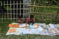 Children lay out their wet textbooks to dry following the landfall of Cyclone Amphan in Khejuri area of Midnapore, West Bengal, on May 21, 2020