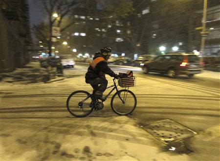 A restaurant delivery person rides his bike through the West Village neighbourhood as snow begins to fall in New York January 2, 2014. REUTERS/Gary Hershorn