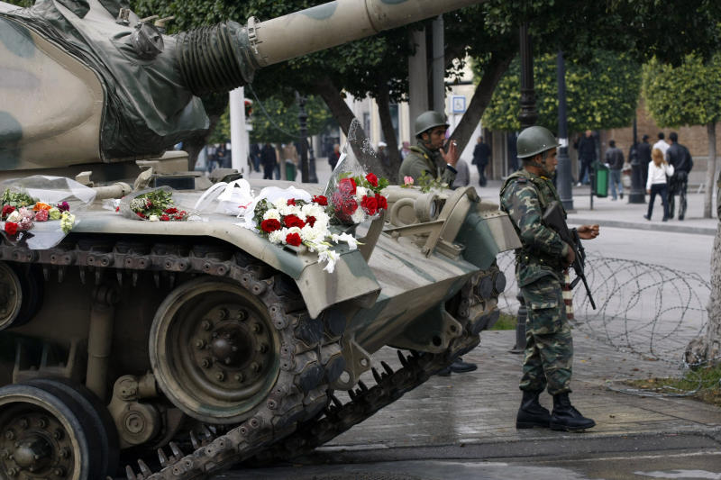 FILE - In this Tuesday, Jan. 18, 2011 file photo, flowers are displayed on a tank as soldiers guard the center of Tunis. Tunisia's president on Thursday March 6, 2014 lifted the state of emergency that has been in place since the outbreak of a popular revolution three years ago, and a top military chief said soldiers stationed in some of the country's most sensitive areas will return to their barracks. (AP Photo/Christophe Ena, File)