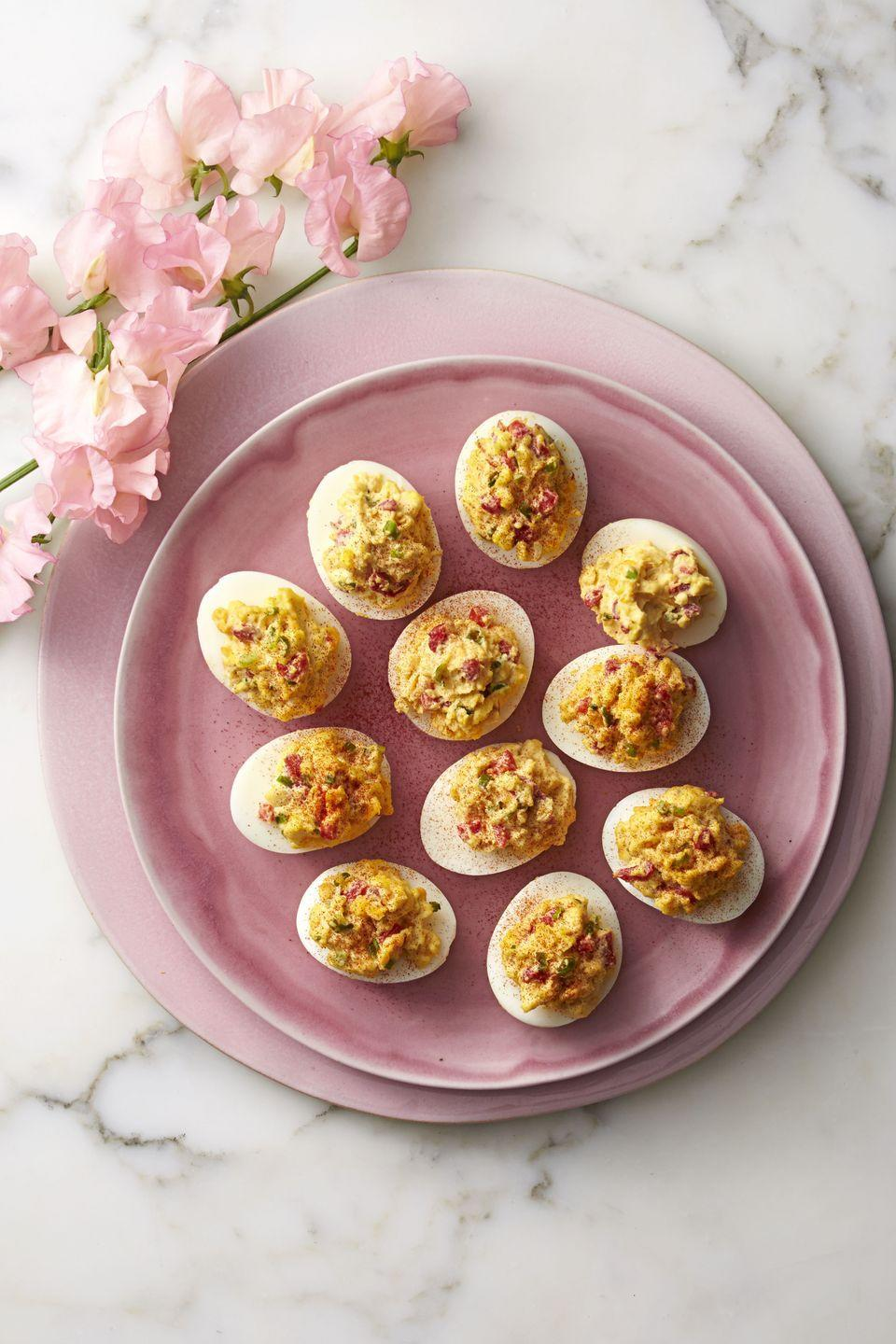 """<p>It's like rolling two classic Southern snacks into one. You can make these stuffed eggs up to a day in advance; simply serve when guests arrive.</p><p><strong>RELATED</strong>: <a href=""""https://www.goodhousekeeping.com/food-recipes/easy/g606/deviled-eggs-recipes/"""" rel=""""nofollow noopener"""" target=""""_blank"""" data-ylk=""""slk:30 More Ways to Make Delicious Deviled Eggs"""" class=""""link rapid-noclick-resp"""">30 More Ways to Make Delicious Deviled Eggs</a></p><p><a href=""""https://www.goodhousekeeping.com/food-recipes/a37454/pimiento-cheese-deviled-eggs-recipe/"""" rel=""""nofollow noopener"""" target=""""_blank"""" data-ylk=""""slk:Get the recipe for Pimiento-Cheese Deviled Eggs »"""" class=""""link rapid-noclick-resp""""><em>Get the recipe for Pimiento-Cheese Deviled Eggs <em><em>»</em></em></em></a><em> <br></em></p>"""