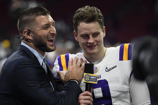 LSU quarterback Joe Burrow (9) speaks with former NFL player Tim Tebow after the Peach Bowl NCAA semifinal college football playoff game against Oklahoma, Saturday, Dec. 28, 2019, in Atlanta. LSU won 63-28. (AP Photo/Danny Karnik)