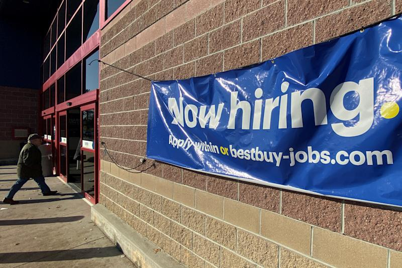 """A """"Now Hiring"""" sign advertising jobs at Best Buy hangs outside a store in Salem, New Hampshire, U.S., November 25, 2019. REUTERS/Brian Snyder"""