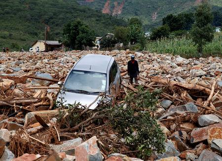 A woman stands besides a car that was swept away with debris by Cyclone Idai in Chimanimani, Zimbabwe, March 23,2019. REUTERS/Philimon Bulawayo
