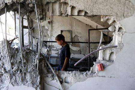 A child inspects site hit by what activists said was airstrike by forces loyal to Asaad at Arbin town in Damascus countryside, Syria