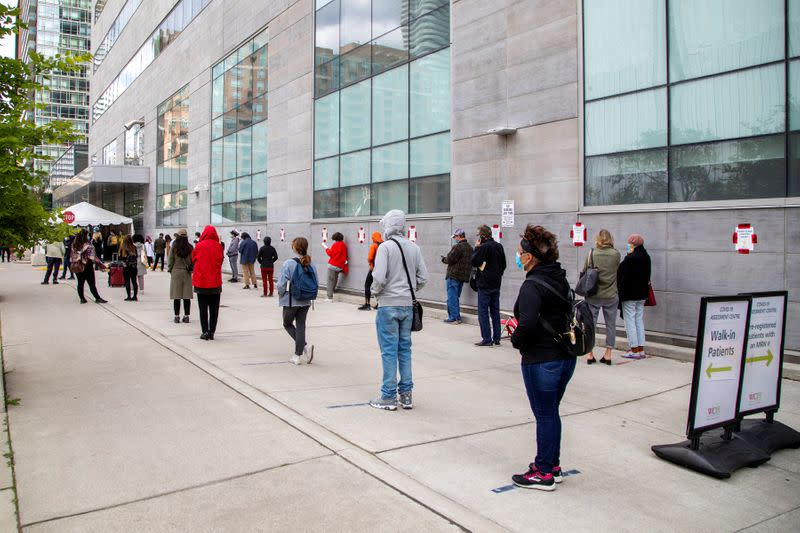 FILE PHOTO: People wait in line at a coronavirus disease (COVID-19) testing facility in Toronto.