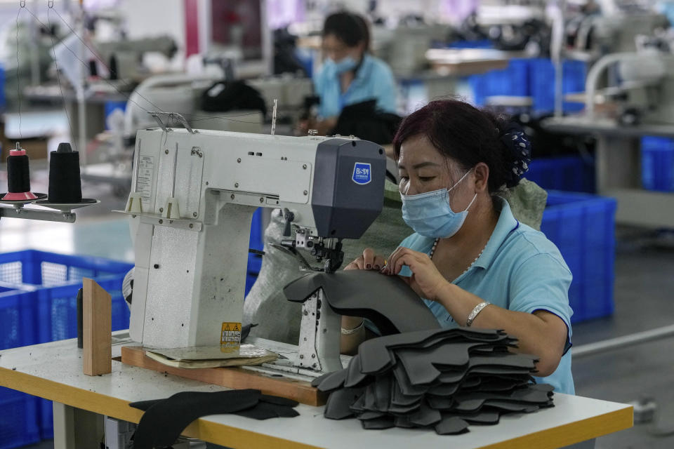 FILE - In this July 15, 2021, file photo, workers wearing face masks to help curb the spread of the coronavirus sew layers for ice-skating shoes at a factory in the ice and snow sports equipment industry park in Zhangjiakou in northwestern China's Hebei province. Shortages of power, computer chips and other parts, soaring shipping costs and shutdowns of factories to battle the pandemic are taking a toll on Asian economies. (AP Photo/Andy Wong, File)