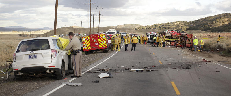 Investigators work the scene of a crash site where a truck carrying a prison inmate fire crew collided with a car, left, on a narrow highway north of Los Angeles near Gorman, Calif., on Tuesday, Nov. 23, 2010, killing one inmate and one person from the car and leaving a dozen people injured. (AP Photo/Antelope Valley Press, Troy Harvey) MANDATORY CREDIT